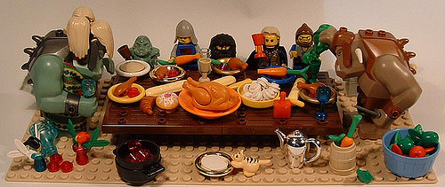 A photo of lego figurines posed around a table laid out for Thanksgiving.