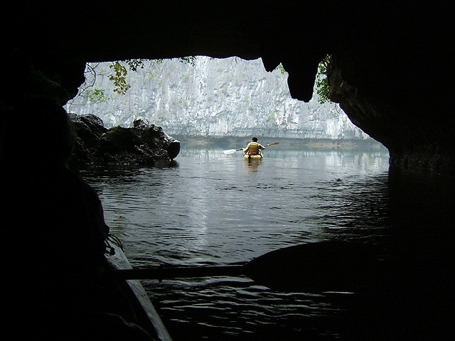 Photo of person in kayak leaving cave